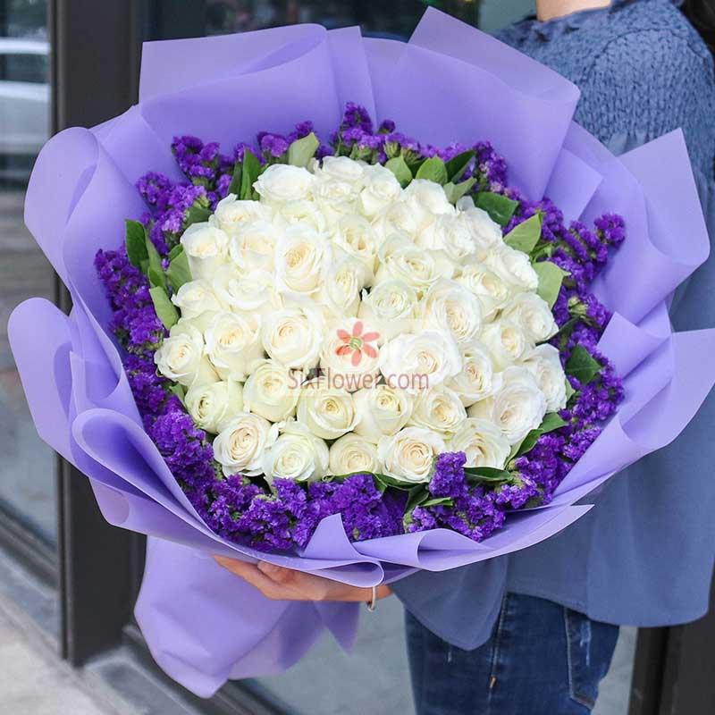 33朵白玫瑰,周围紫色勿忘我丰满,栀子叶搭配